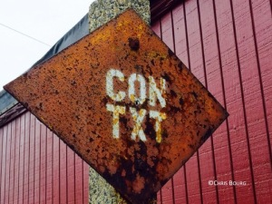 "Rusty sign with ""CON TXT"" written on it, spotted near abandoned train tracks"